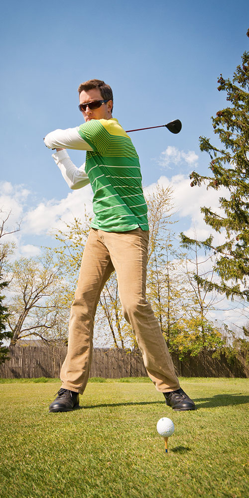 Man playing golf about to swing for ball